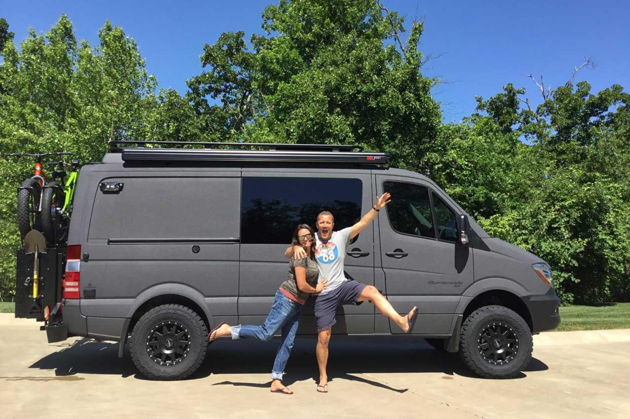 5960ddbdc1 A gun metal grey Sportsmobile 4x4 custom camper van conversion with happy  owners standing next to it.