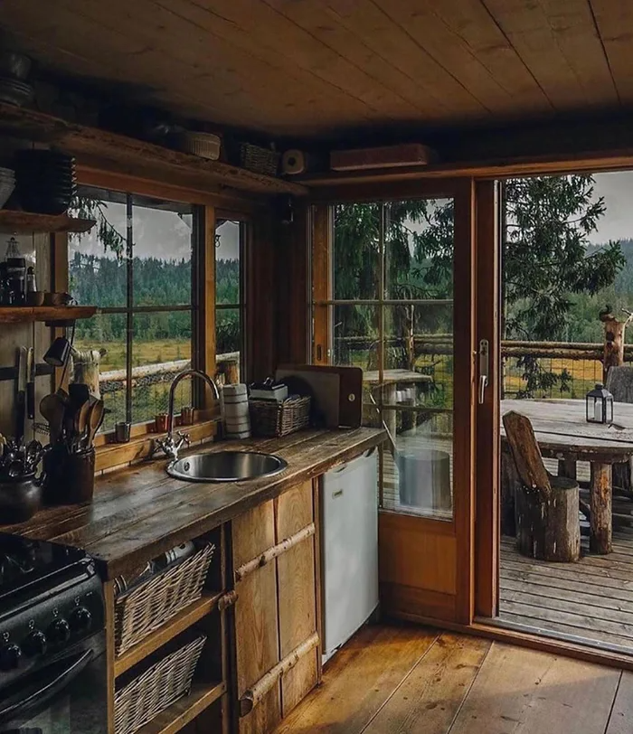 Rustic cabin kitchen opening up to a deck overlooking the wilderness of Veldre Almenning, Innlandet, Norway - Cozy & Comfy