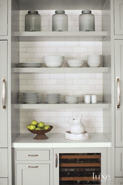 Gray kitchen cabinets with open shelving and white subway tile also