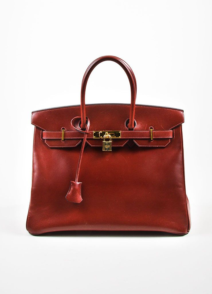 486aa731dc3b This 35cm size Birkin handbag is constructed of rich oxblood red box calf  leather with gold toned metal hardware. Two rolled top handles.
