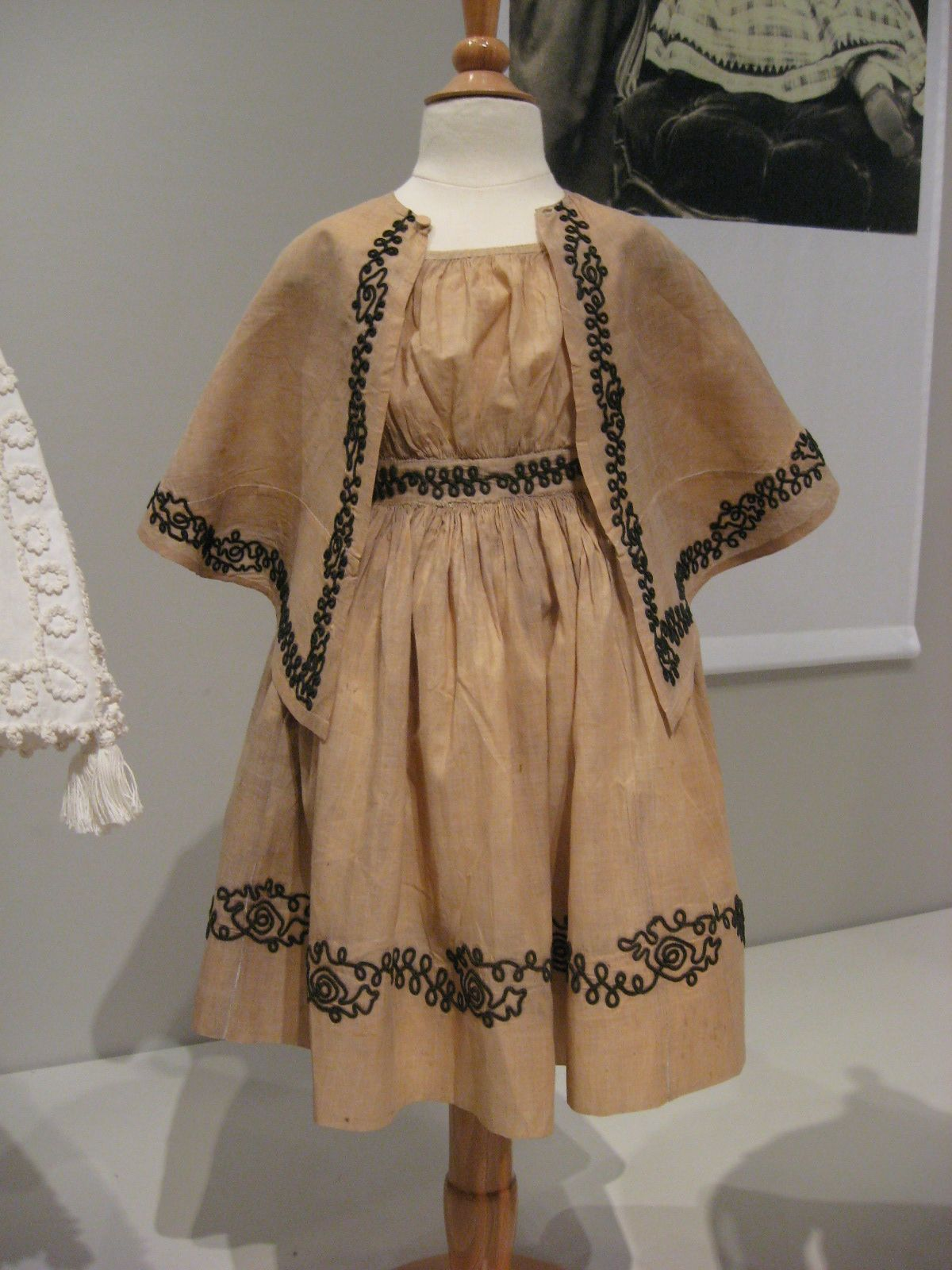 2012-08-25 KSMF - Child's dress and capelet made of tan linen with black braid trim, circa 1863.