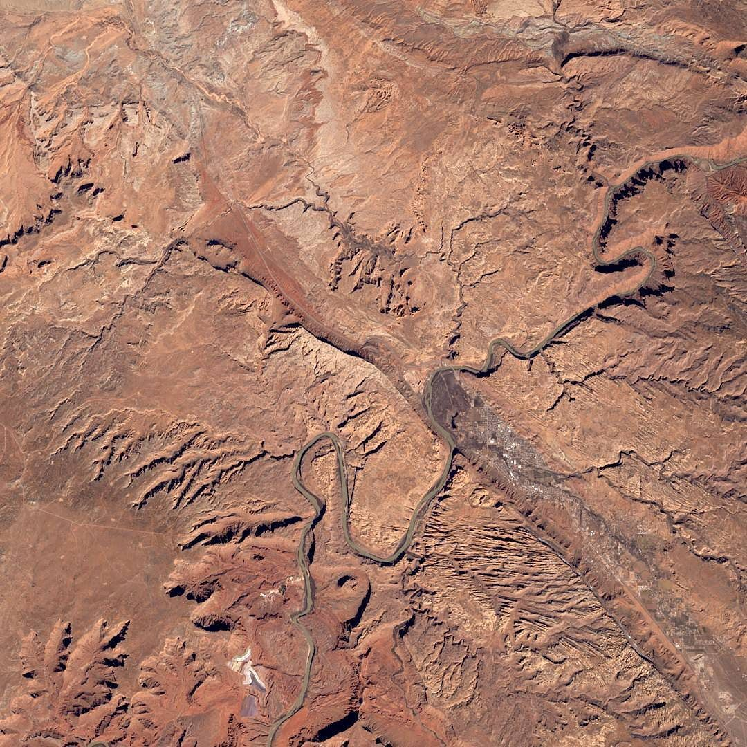 On Feb 28 2016 Landsat 8 passed over the Colorado Plateau on a cloudless day and acquired this image of Southeastern Utah. The green-gray muddy Colorado River winds down from the upper right to the bottom middle. US Highway 191 makes a straighter line from the upper left to the lower right crossing the Colorado River on the edge of Moab Utah the county seat of Grand County and a popular vacation destination. About this time of year hikers mountainbikers climbers and off-roaders descend on…