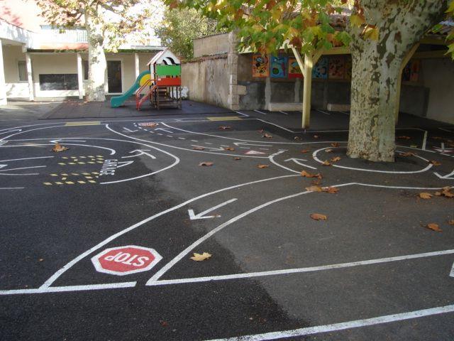 een verkeersparcours op de speelplaats geschilderd