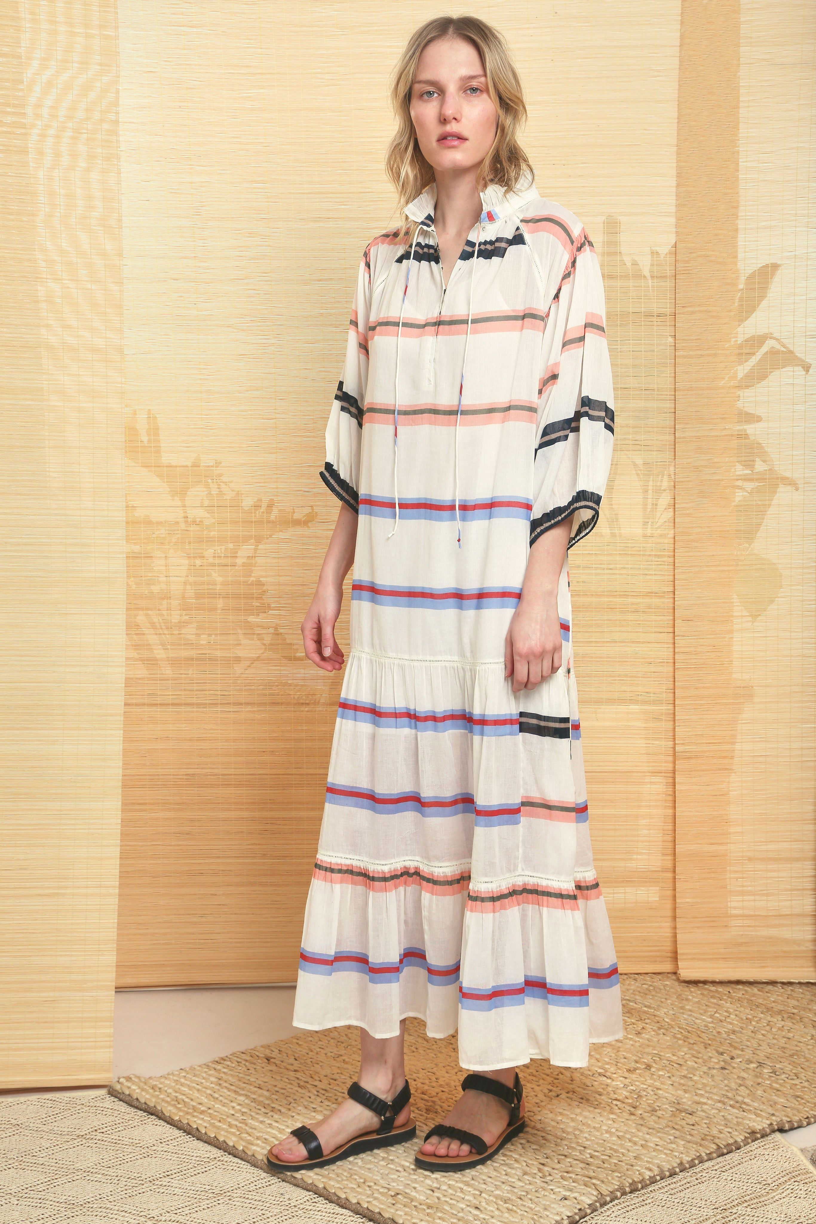 THIS SEASON'S DREAM DRESS FOR EASYGOING VACATION TRANSITIONS – FROM BEACH TO HITTING THE TOWN FOR COCKTAILS OR SUNSET DINNERS. CUT FROM A LIGHTWEIGHT, BREATHABLE COTTON PRINTED WITH BOLD STRIPES, DELICATE RUFFLE DETAILING AROUND THE COLLAR, HOOK AND EYE CLOSURE UP THE FRONT, ¾ SLEEVE, AND FULL MAXI SKIRT.