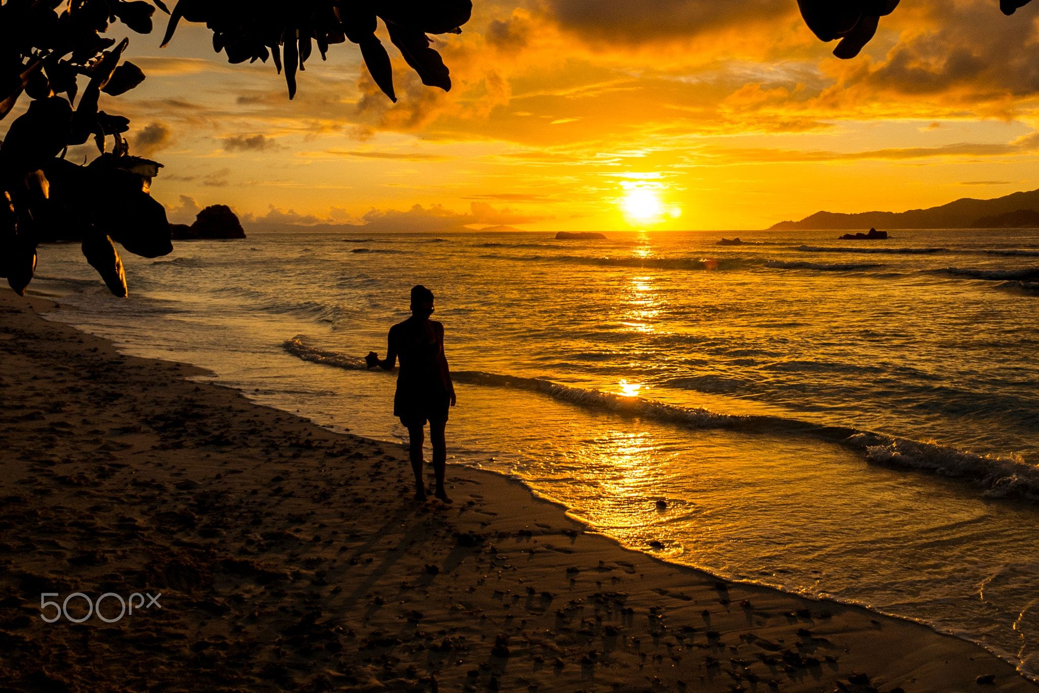 Young woman walking and relaxing in the sunset - Young woman walking and relaxing in a tropical beach on the sunset, Anse severe, La Digue, Seychelles