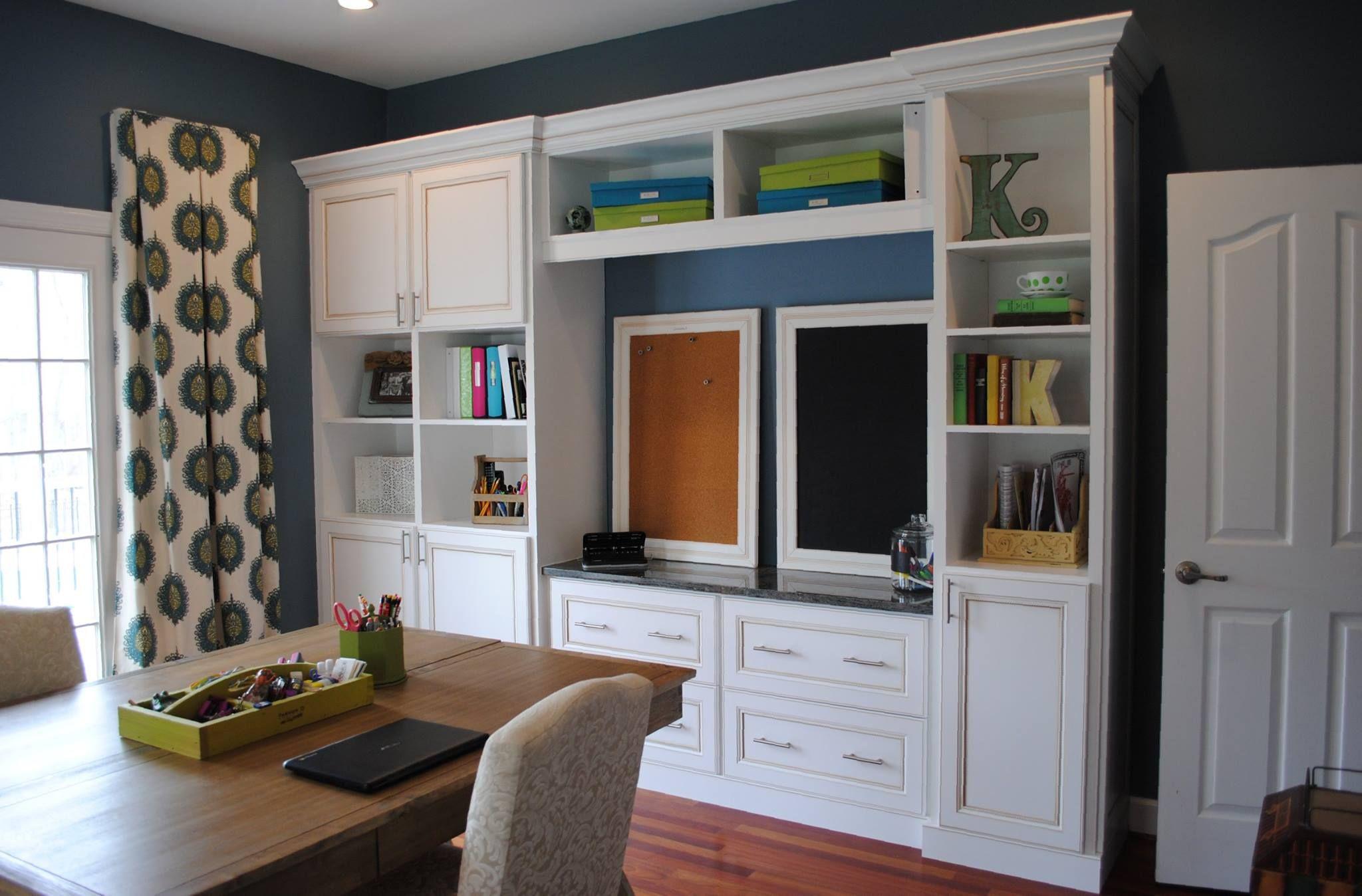 A white melamine wall unit w glazed cabinet doors & molding creates