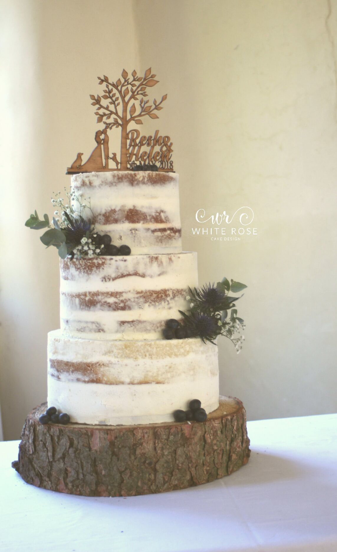 Semi-naked wedding cake with sea holly and fresh flowers with wooden ...