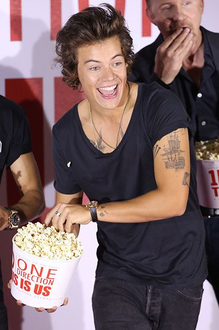 Harry Styles throws popcorn during the One Direction This is Us 3D press event in London on August 19. Harry's actually just feeding the photographers!