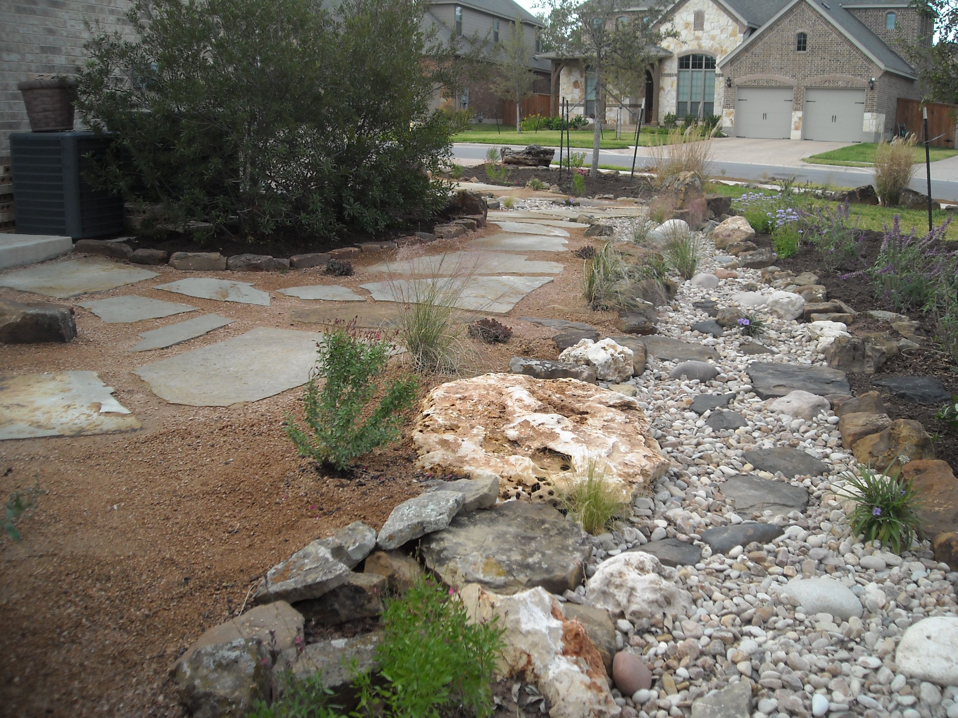 Front yard landscape dry creek bed with a natural flagstone