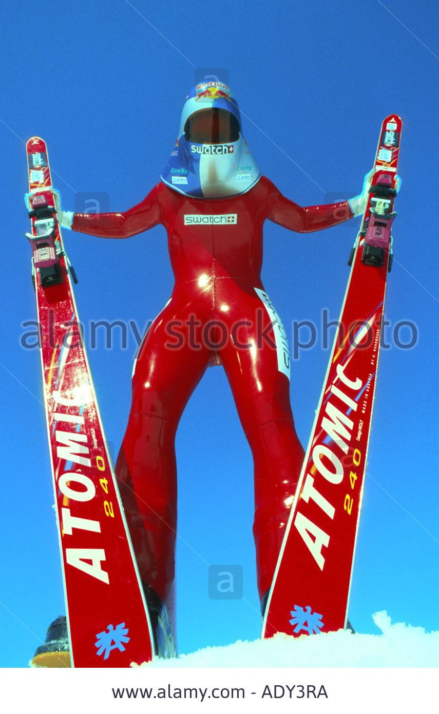 high speed skiing, wearing racing suit and helmet, holding ski Stock Photo