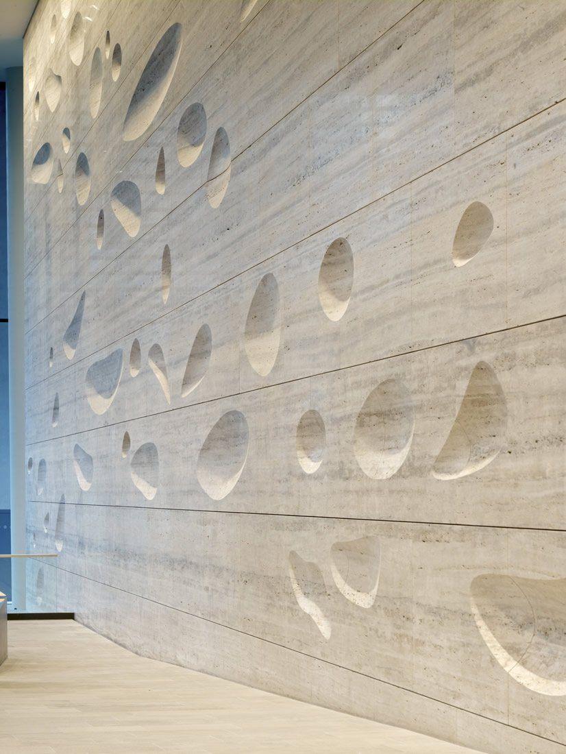 Sculpted travertine wall by Kohn Pedersen Fox