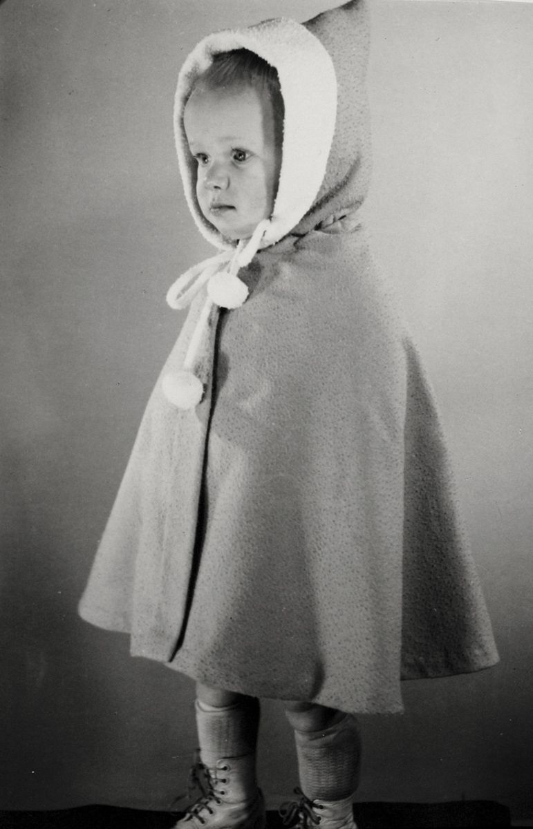 Peuter in cape met capuchon en strik met pomponnen. Nederland, 1950 ...