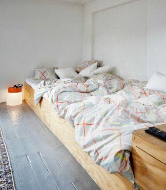 Doppelbett mit 3-teiligem IKEA PS 2014 Bettwäsche-Set in Bunt, daneben IKEA PS 2014 Leuchthocker in Orange