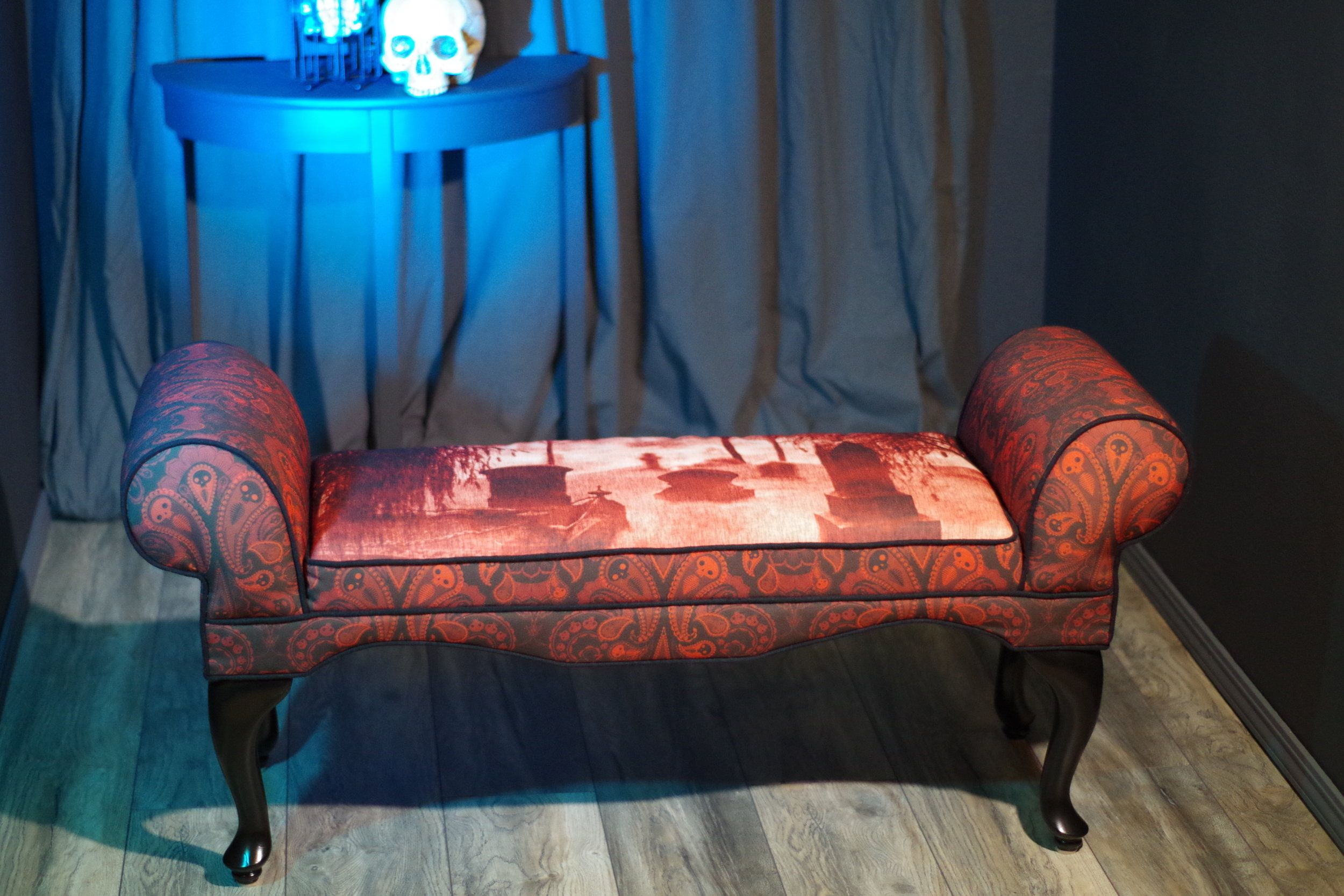 Cemetery Bench from $305.00 Classic style meets dark whimsy in this victorian-style piece.  The top of the seat features a scene from the Kawaiahao church cemetery in Hawaii, while a playful 'Ghost Paisley' pattern compliments the rest of the upholstery.   Finished with black, linen-blend welt trim. Color(s): Red and black  Material(s): Upholstery: 100% polyester Eco Canvas, made from 45% recycled material.