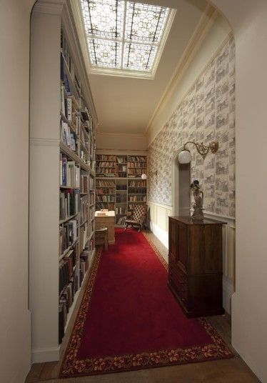 A beautiful ornate roof window allows light to flood into this long narrow library