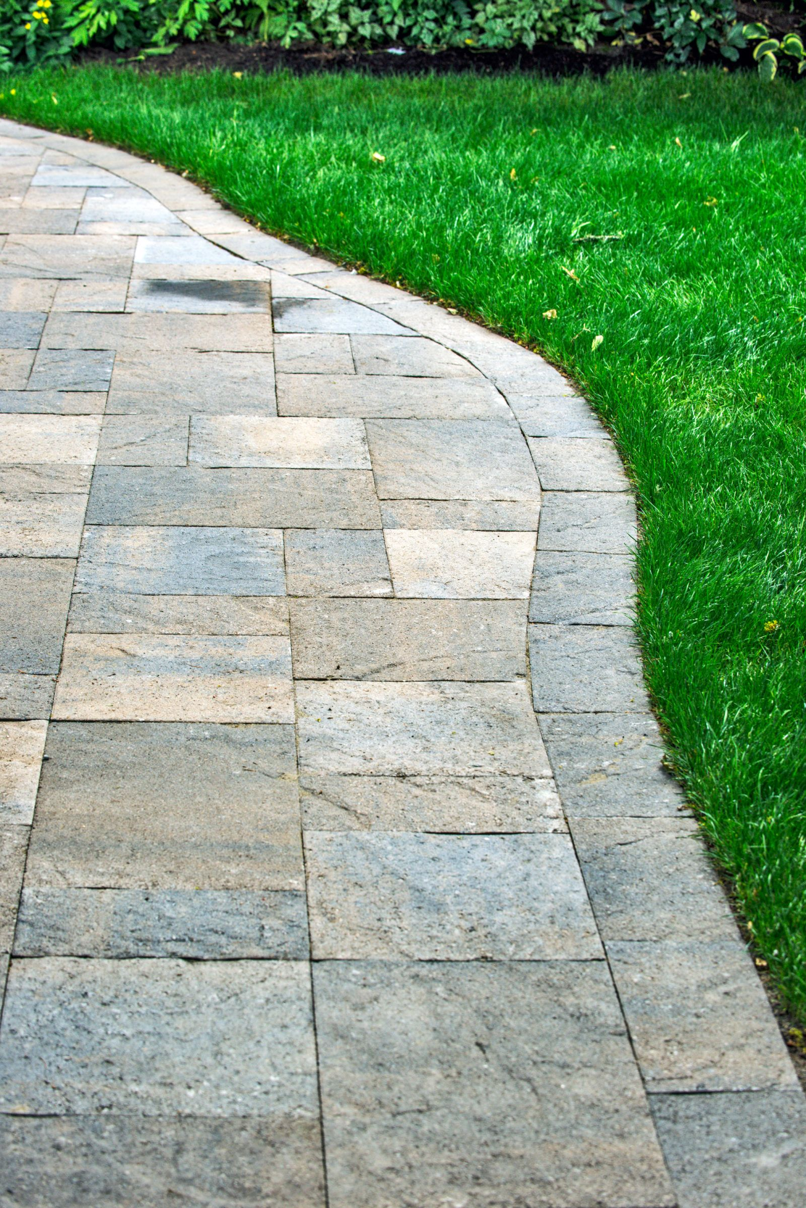 This modern outdoor living room features a Columbia Slate patio, RomanStack  tree ring planter, stone veneer food service area and a flagstone path.