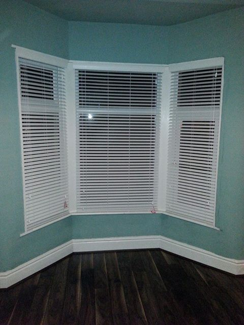 Liverpool White faux wood venetian blinds fitted into a bay window