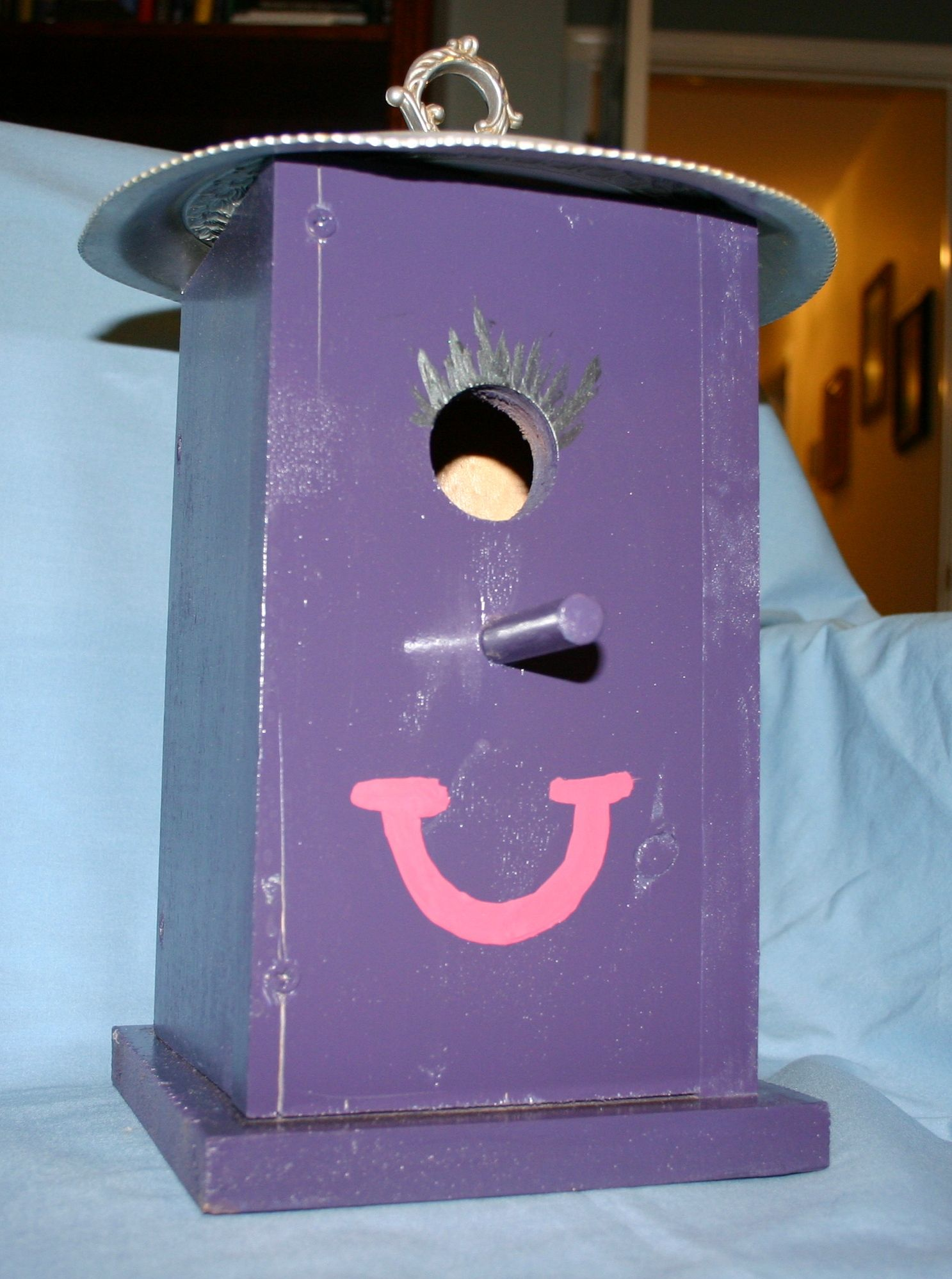 One-eyed purple people eater bird house.  Made with materials from my scrap bin.  Roof is lid from a soup terrain.  Painted by my daughter.