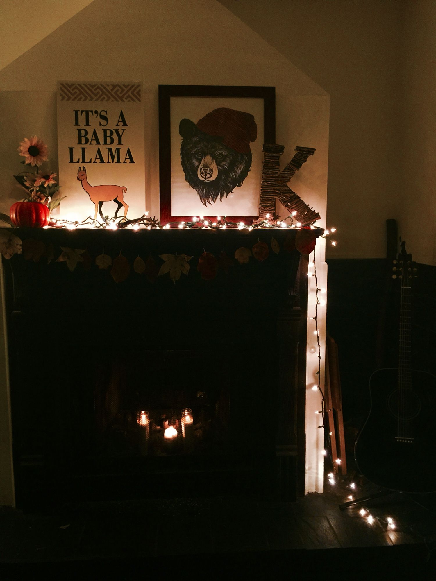 Fall mantel with lights, leaf garland, pumpkin, sunflowers and acoustic guitar.