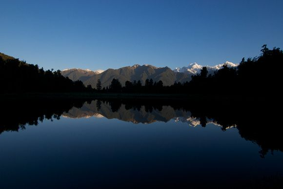 This is Lake Matheson, New Zealand on an unusually calm and clear day. You can see the reflection of Aoraki (Mt. Cook) and Mt. Tasman in the lake