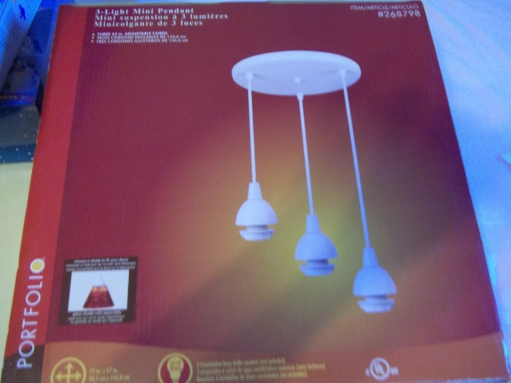 """Porftolio 3 light mini pendant in white. Has 3- 53""""adjustable cords. It is 12"""" x 57"""". Choose a shade to fit your decor-they are not included. This is 3 lights in a semi-circle.new in box. Stores."""