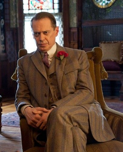 Nucky Thompson -Atlantic City Treasurer, played by Steve Buscemi. Nucky Thompson sits in a yellow chair in the parlor of Chalky White's house.  1920s prohibition era, early 20th Century American period dramas, late-Victorian, early Art Nouveau and Arts homes, vintage/retro 1920s men's gangster suits clothing fashion, vintage inspired pinstripe suit
