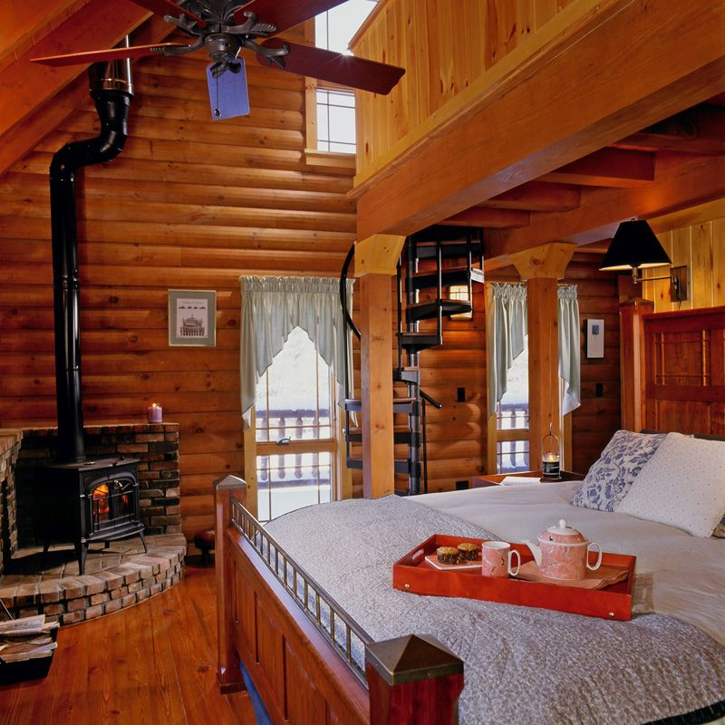 Woodstove In A Log Cabin | Log Home Bedroom With Wood Stove And Spiral  Staircase