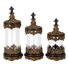 """Three lidded canisters with fleur-de-lis finials.Product: Small, medium and large canisterConstruction Material: Resin and glassColor: Brown and clearFeatures: Will enhance any décorDimensions:  Small: 13"""" H x 6"""" Diameter  Medium: 15"""" H x 6"""" Diameter Large: 17"""" H x 6"""" Diameter"""