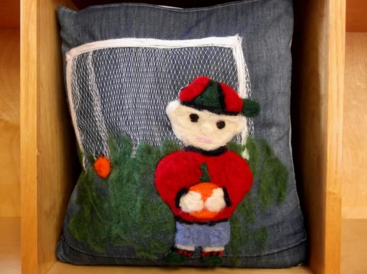 A simple cushion made from recycled denim, machine felted & embellished with a machine felted footballer motif. The goal post netting is from recycled from a fruit punnet.