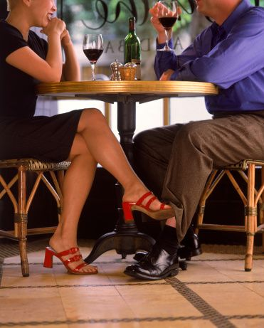 Woman Playing Footsie With Man At A Restaurant Foot Under The Table Legs
