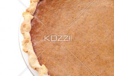 close-up cropped image of pumpkin pie. - Close-up cropped image of pumpkin pie served over white background.