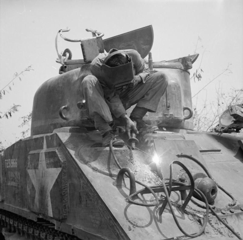 f413855522b54 A REME welder repairing battle damage on a Sherman tank at 5th Indian  Division s tank workshops near Taungtha