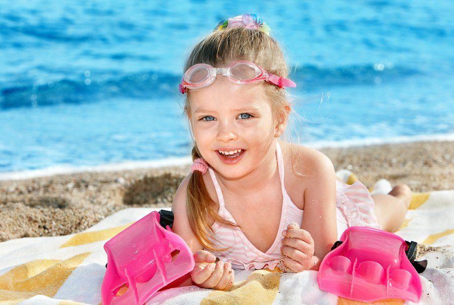 Pequeña niña en la playa, con su traje de baño, recostada en una toalla, sobre la arena. Wallpaper.