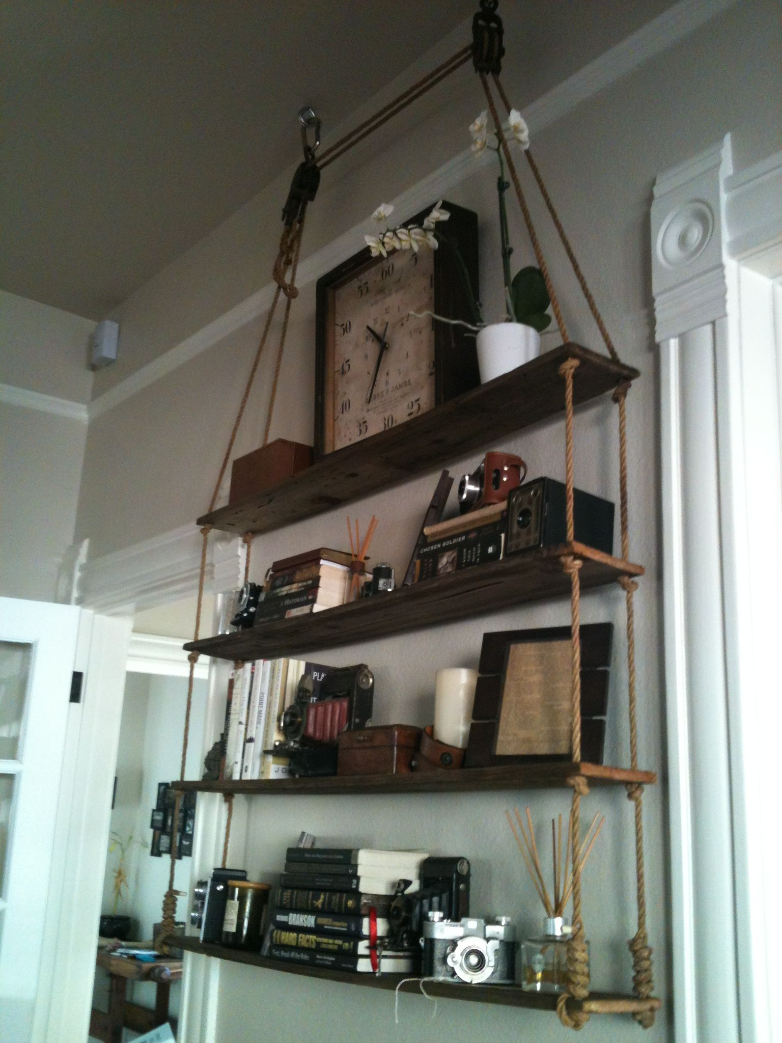 Hanging rope shelves with pulleys and old fence boards as shelves