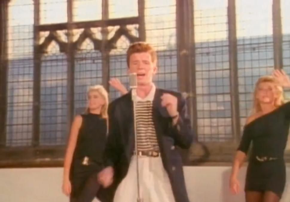 In The Never Gonna Give You Up Music Video Directed By Simon West A Smiling Rick Astley Sings And Dances To The Song In Various Outfits And Venues In West L