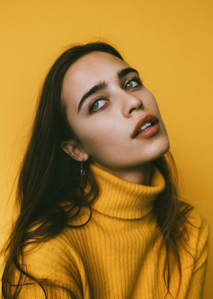 Model Lera Pentalute in a vibrant yellow photoshoot.  Styled with a yellow turtleneck and yellow backdrop