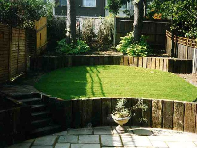 Circular raised lawn with indented patio as central feature of a small garden (Terrace garden, Lewisham | Terrafirma Landscapes).