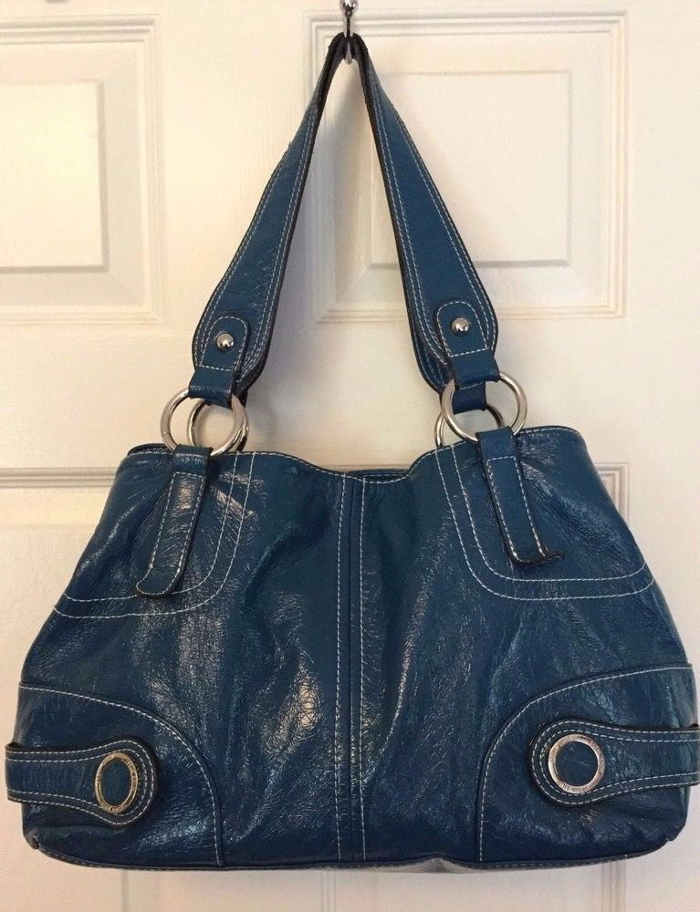 This large shoulder bag is made of a shiny teal polyurethane and has bright silver  metal accents, a snap closure, ... 40153cd2ff