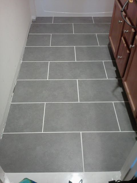 Staggered placement mitte gray 12 x 24 tile from lowes for Grey bathroom laminate flooring