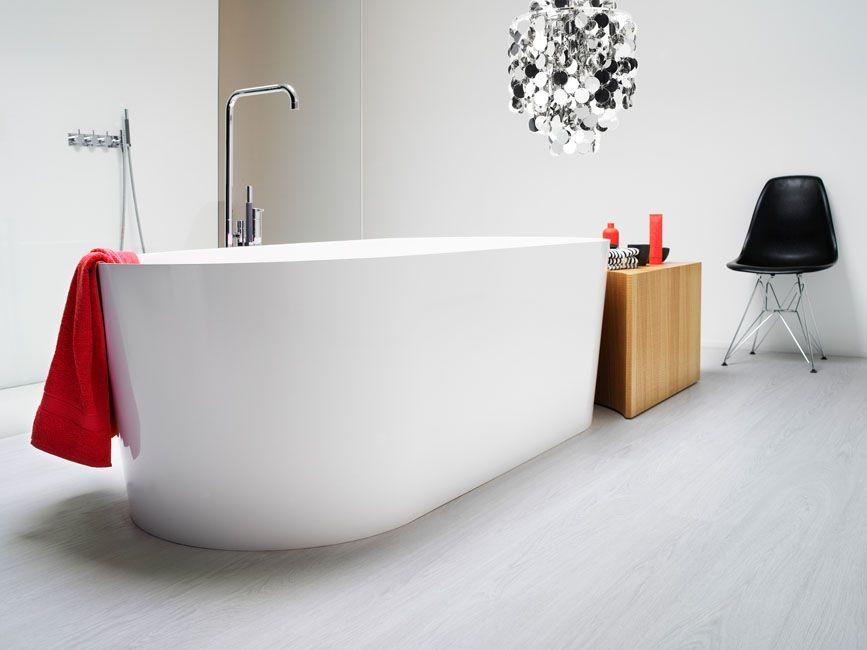 une baignoire blanche très design trône au milieu d\'une pièce rvêtu ...