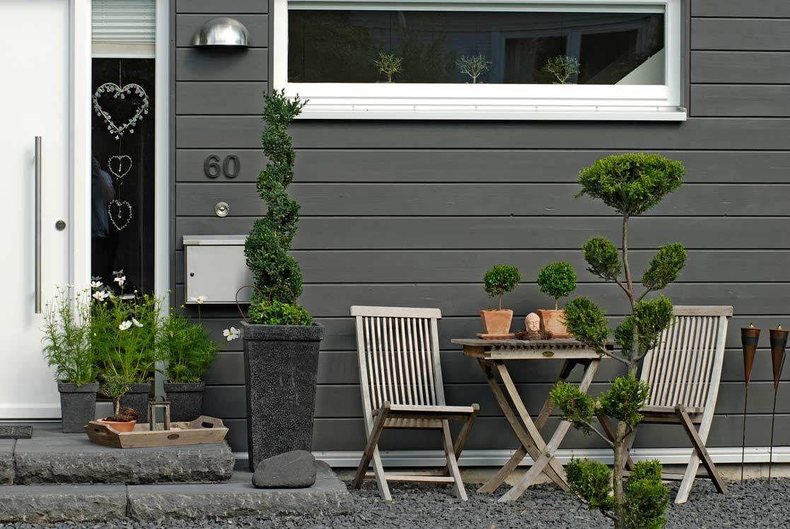 Kontrastreiche Fassade mit weißen Tür- und Fensterelementen und ...