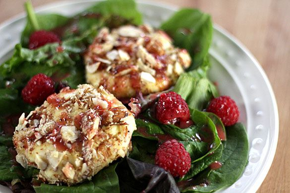 Warmed and crispy goat cheese salad combines greens that are topped with a crusted goat cheese and highlighted with raspberries and a raspberry dressing.