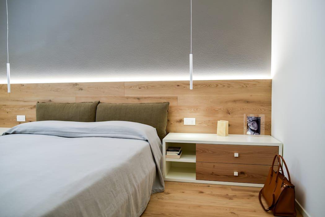 Photo of Camera da letto con parete posteriore in legno con illuminazione indiretta