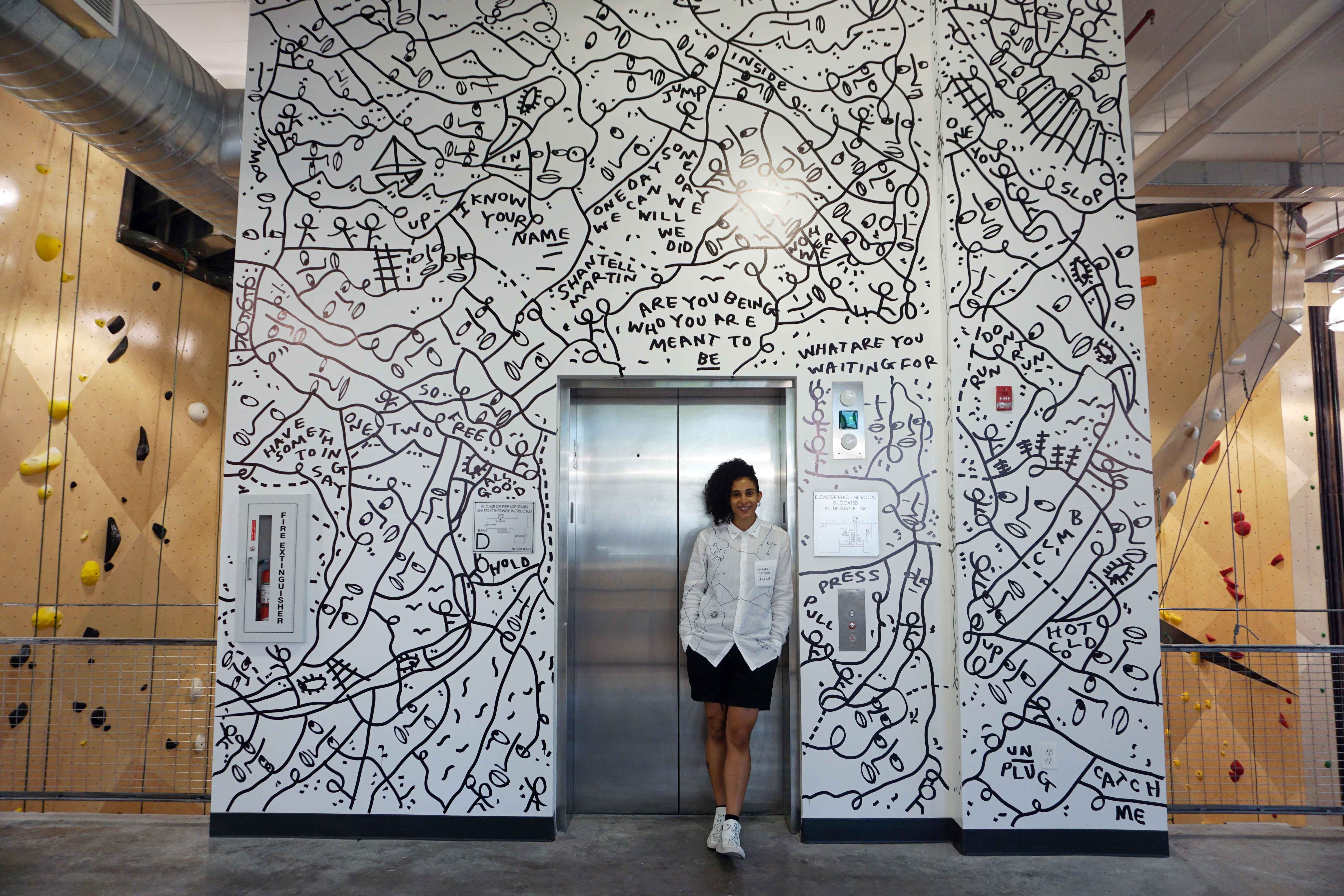 Meet Shantell Martin, an artist famous for her free-form drawing style. Her latest mural is on some of our walls at Brooklyn Boulders Queensbridge.
