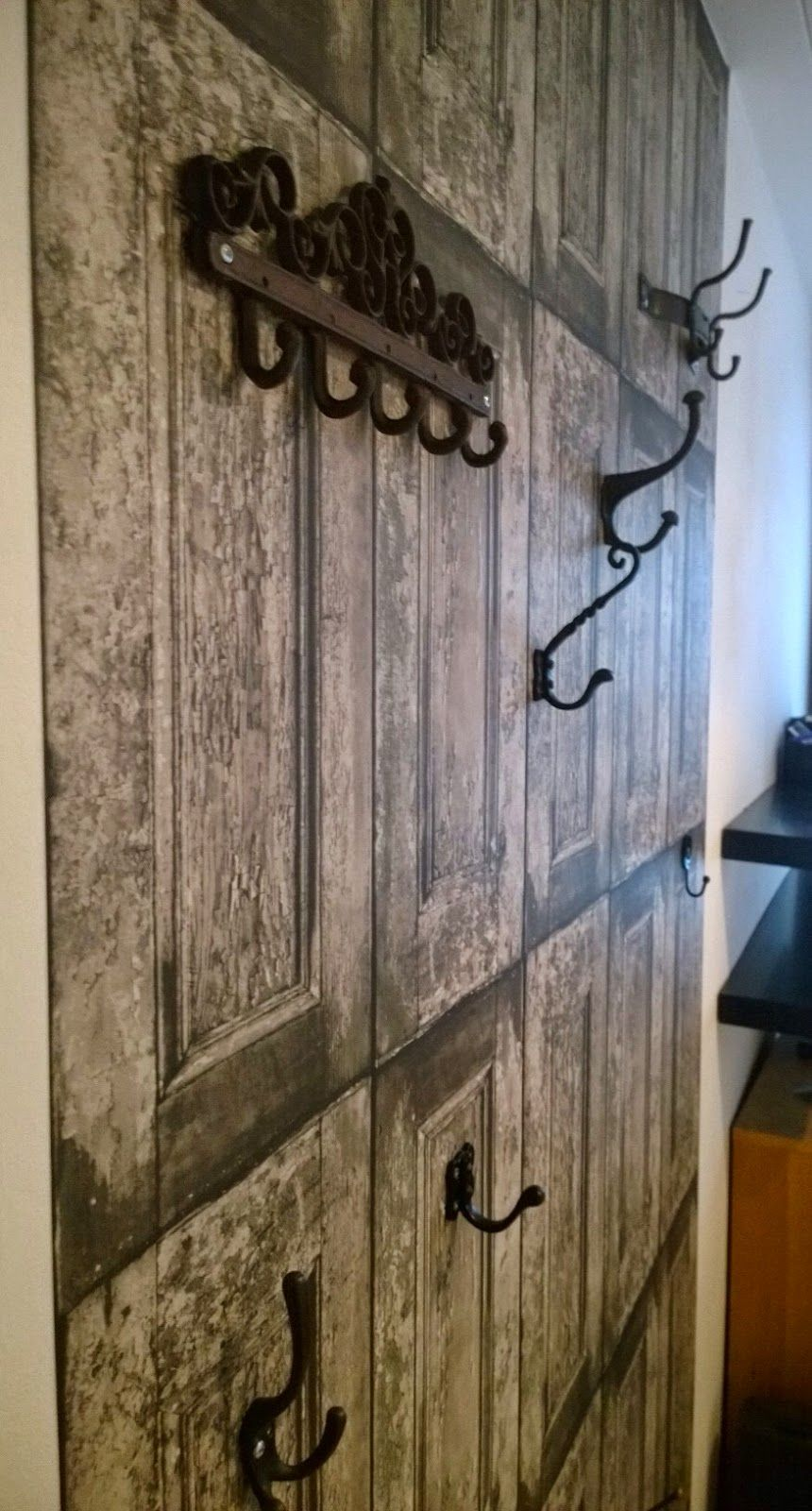 Rustic coat rack from wallpaper and different metal hooks.