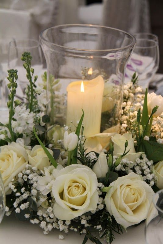 Hurricane Lamps Surrounded By Wreaths Of Fresh Spring Blooms Including Roses Stocks And Hydrangeas