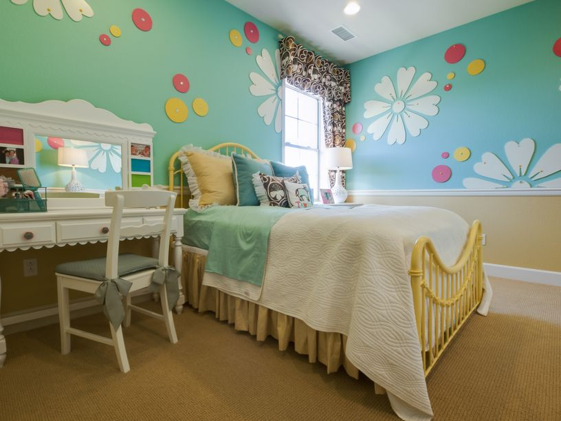 This bright blue girl's room has whimsical polka dots and flowers to break up the solid wall color.