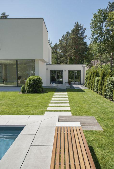 Moderne Außenanlage, die Platz für Grün lässt: Großformatige silkstone® Platten als Poolumrandung und Weg. #rinnbeton #design #gartengestaltung #vorgartenlandschaftsbau