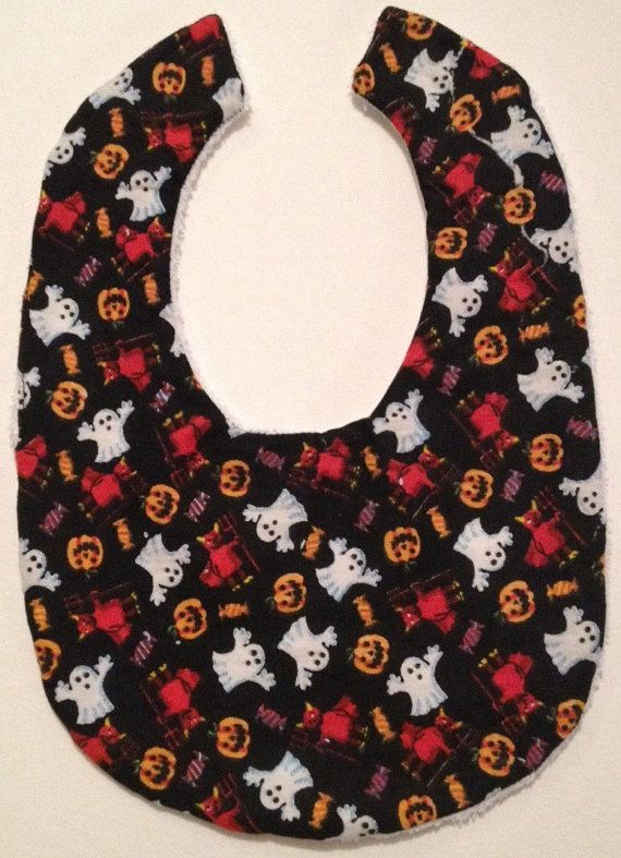 This is a cool handmade bib featuring a spooky ghost, devil, pumpkin & candy print on black with black towelling backing.  Also available as a bandana bib. Would make a great baby shower gift, a thoughtful pressie to spoil a mum to be or just keep them for your little one. The bib is thick and absorbent so perfect for keeping little ones dry, clean and stylish.  Made with soft cotton and backed with terry towelling.  Dimensions: 28cm x 19cm approx  Machine washable and iron on printed side…