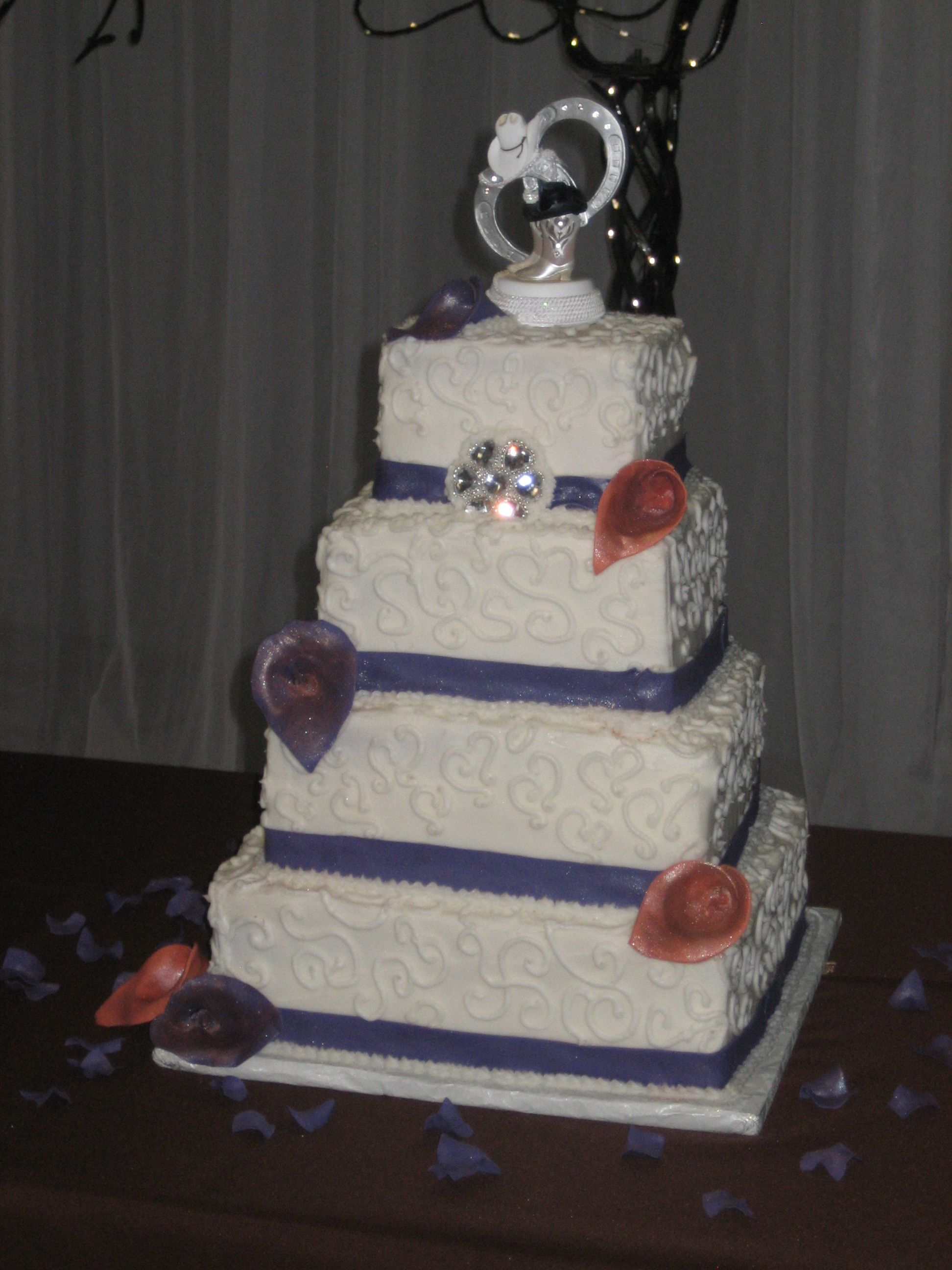 Country-themed cake with cowboy hats, boots and wagon